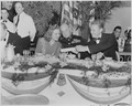 Photograph of movie stars Constance Moore and Van Johnson, seated at a table with an unidentified military officer... - NARA - 199324.tif