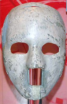 the mask is white and of solid construction, with egg-sized oval cutouts for the eyes and a rectangular cutout from the base of the nose to below the lower lip