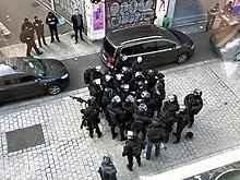 Trois groupes de policiers (un de deux, un de quatre et un de vingt-six) en uniforme avec armes et protection pour la plupart attendent sur la rue de la République.