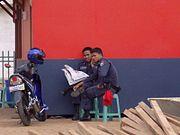 Dua orang Polisi Pamong Praja sedang membaca koran