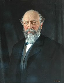 Portrait of a balding middle-age man with grey hair and beard, wearing a dark overcoat over a blue jacket and white shirt.