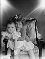 Portrait of a young girl sitting on an armchair with a baby on her lap (AM 74962-1).jpg