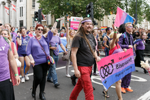"A group of men and women, dressed in purple, pink and blue, marching down a street with a banner which reads ""Out and proud - Bisexuals! - Fighting for equality"""