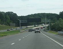 Ground-level view of a four-lane divided highway with a wide grassy median separating the opposing lanes of traffic; in the distance the road makes a sharp curve. A black electronic sign without lettering is visible above the highway.