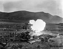 Several artillery guns fire in unison in a field
