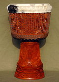 Djembe decorated with extensive carvings on the stem and bowl, with folded-over skin