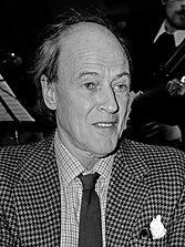 A greyscale picture of Roald Dahl wearing a shirt, tie, and sports jacket