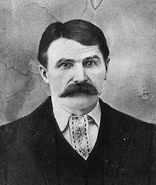 A head and shoulders shot of a middle aged white man with dark hair parted on his right and a full moustache, wearing a jacket and vest.