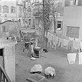 Ruimte tussen woningen met een Jeminitische vrouw aan de was en wasgoed aan de w, Bestanddeelnr 255-1300.jpg