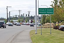 "A wide suburban road with several parking lots. At the right of center is a sign reading ""William P. Stewart Memorial Highway""."