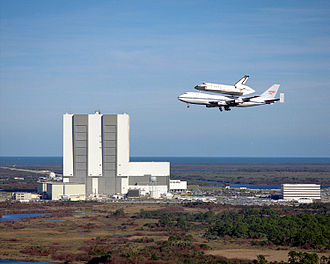 Shuttle Carrier Aircraft - Columbia atop SCA N905NA, flying by the Vehicle Assembly Building (VAB) at Kennedy Space Center (KSC), 1990. N905NA no longer has American Airlines' pinstriping.