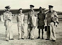 Five men in World War II military uniforms, standing on an airfield