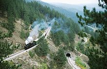 Steam passenger train on a winding, mountainous switchback