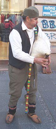 Serbian bagpiper in traditional attire wearing opanci and šajkača.