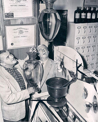 Show globe - Two pharmacists in Ferndale, Michigan hanging show globes, 1954.