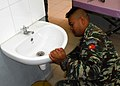 Soldier repairs a leaky sink at the Manatuto Maternity Clinic.jpg
