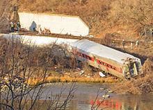 An area of land with brown vegetation lit by golden late-afternoon sunlight next to water and railroad tracks in the background at the base of a steep hill with a white concrete retaining wall. A silvery rail car lies along the shore, almost all the way to the water, with its windows either broken out or severely cracked. Behind it is another car, lying almost on its side.
