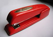 "A small red stapler with the badge reading ""Swingline"" atop, seen from above on a white background with shadow at the top of the image"