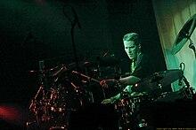 Ударник с Ежик, носить черную футболку, сосредоточенно играет его большой барабан, установленный в центре внимания.