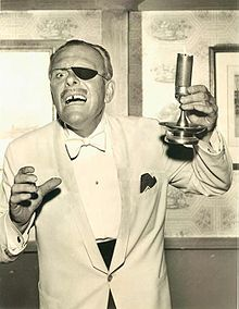 Terry-Thomas wearing a white dinner jacket. He wears an eye-patch and carries a candle