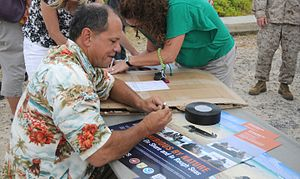 Patrick Ching - Ching autographing copies of a newly released poster featuring Marine Corps Base Hawaii efforts to protect Hawaiian monk seals during an unveiling ceremony, May 23, 2012