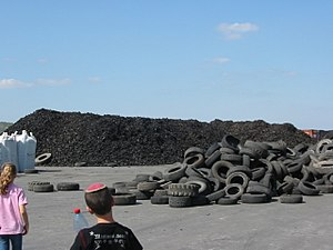 Tire recycling - Used tires in foreground waiting to be shredded and shredded tires in background.