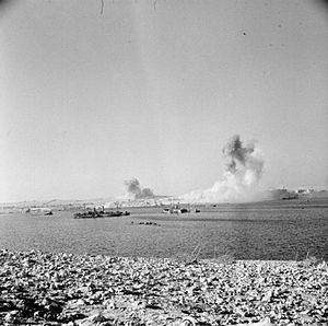 89th (Cinque Ports) Heavy Anti-Aircraft Regiment, Royal Artillery - German bombs explode during one of the heaviest air raids on Tobruk. The photograph was taken from a trench adjoining an AA gun.