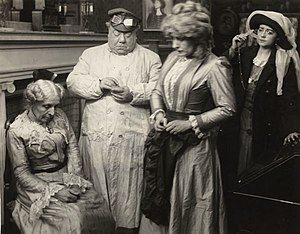 "John Bunny - Scene still from the 1911 Vitagraph production ""Treasure Trove."" Left to right are Mary Maurice, John Bunny, Julia Swayne Gordon, and Helen Gardner."