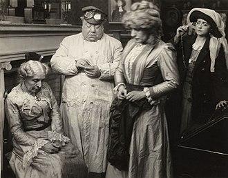 "John Bunny - Scene still from the 1911 Vitagraph production ""Treasure Trove."" Left to right are Mary Maurice, John Bunny, Julia Swayne Gordon, and Helen Gardner."