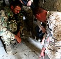 U.S. Marine Corps Gunnery Sgt. Charles Evers, right, an infantryman with Black Sea Rotational Force 11, draws a diagram on the floor for a Georgian soldier during military operations in an urban terrain training 110719-M-OS573-001.jpg