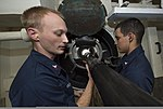U.S. Navy Sonar Technician (Surface) 1st Class Christof Bessler, left, and Sonar Technician (Surface) 2nd Class Charles Granger inspect the locking bolt screws on a multi-functional towed array (MFTA) module 140103-N-PW661-015.jpg