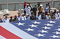U.S. Service members and veterans gather around a U.S. flag during a Memorial Day celebration at the Intrepid Sea, Air and Space Museum in New York May 27, 2013 130527-M-DO926-012.jpg