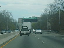 A four-lane freeway in an urbanized area. An overhead sign in the distance reads To George Washington Bridge with a blank variable message sign below it.