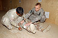 US Army 51039 Spc. Carl Treen, of Northville, Mich., gives an Iraqi Soldier tips on applying a bandage to a leg wound at the Warrior Academy, Sept. 16. Treen is a medic assigned to Company A, 2nd Battalion, 5th Cav.jpg