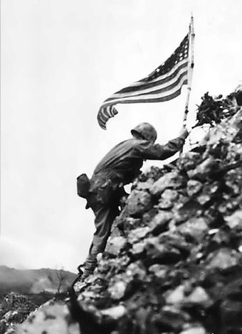 Lt. Col. Richard P. Ross Jr., commander of 3rd Battalion, 1st Marines braves sniper fire to place the United States' colors over the parapets of Shuri Castle on May 30. This flag was first raised over Cape Gloucester and then Peleliu. US Flag raised over Shuri castle on Okinawa.jpg