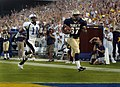 US Navy 040904-N-9693M-005 U.S. Naval Academy Midshipman 3rd Class Jason Tomlinson runs 58-yards on a pass from Quarterback Aaron Polanco for a touchdown, with Duke's John Talley in pursuit.jpg