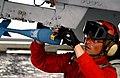 US Navy 060214-N-7711S-113 An aviation ordnanceman attaches a MK-76 practice bombs onto an aircraft on the flight deck aboard the Nimitz-class aircraft carrier USS Ronald Reagan (CVN 76).jpg