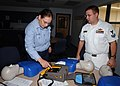 US Navy 061016-N-8544C-001 Hospital Corpsman 2nd class Nicholas Huso instructs Mass Communication Specialist 2nd Class Denise Ordonez how to properly operate an automated external defibrillator (AED).jpg