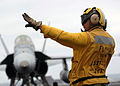 US Navy 070804-N-5384B-154 An Aviation Boatswain's Mate (Handler) directs an F-A-18C Hornet after a recovery at sea aboard Nimitz-class aircraft carrier USS Abraham Lincoln (CVN 72).jpg
