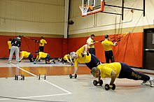 Photograph of US Navy sailors circuit training.