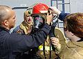 US Navy 111022-N-VH839-028 Damage Controlman Fireman Katelyn Neill gets help donning her firefighting ensemble.jpg