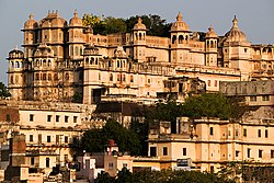 Side view of an ornately decorated palace with several towers on a hill over a city of terraced houses.