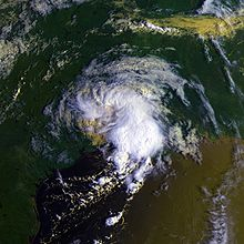 "Satellite image of a tropical storm at crossing the Texas coastline. The storm is in the shape of the number ""9"" with bulging clouds near the bottom. Southeast Texas, northeast Mexico and southwestern Louisiana are visible in the image."