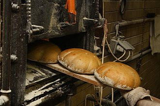 Loaf - A baker takes round loaves of fresh bread out of the oven with a peel