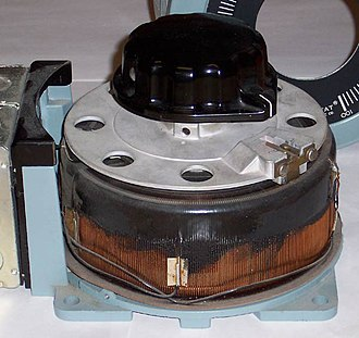 Autotransformer - A variable autotransformer, with a sliding-brush secondary connection and a toroidal core. Cover has been removed to show copper windings and brush.