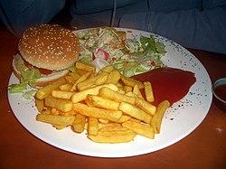 Veggie burger con patatine fritte e insalata
