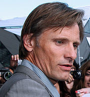 A profile photograph of Viggo Mortensen, a light-haired man wearing a striped collared shirt and a grey blazer.