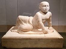 Beige marble statue of a stout young child aged about two years old lying on his left side. The child's head is shaved, his eyes gaze over the viewer's shoulder and his lower body is covered in a draping cloth that hangs limply between his flexed feet, the child supports his torso with his left hand in which he holds an unidentifiable object, he also holds a small bird in his right hand. The sculpture rests on a heavy socle inscribed with barely visible letters spanning the upper part of the socle vertically.