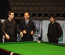 Three men by a snooker table, with Mark Selby on the left and Ding on the right.