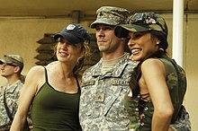 Watros and Bonnie-Jill Laflin posing with a serviceman on a USO tour